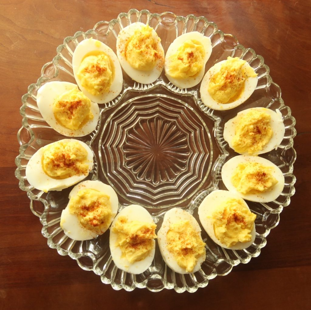 Deviled Eggs on circular crystal platter on wooden table