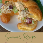 Chicken Salad on a Croissant on a white plate with spinach leaves