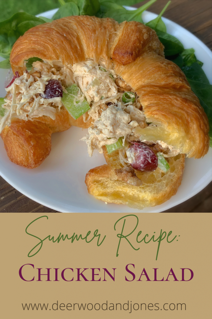 Chicken Salad on a croissant on a white plate and bed of spinach leaves
