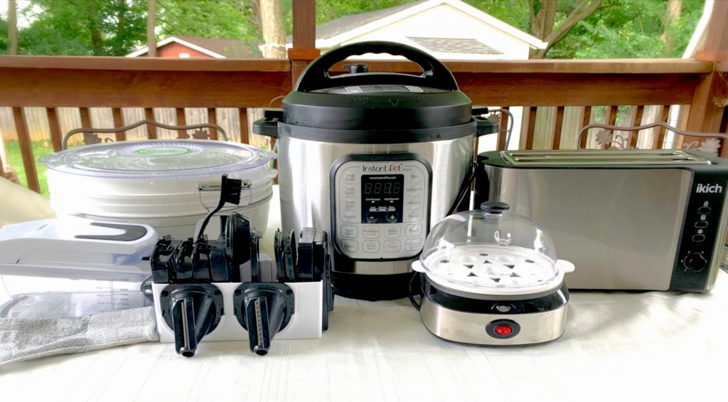 Variety of kitchen gadgets and small appliances on a table outdoors